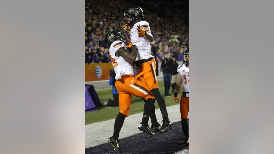 Oklahoma State wide receiver Tyreek Hill, left, celebrates his touchdown with teammate Marcell Ateman, right, during the first half of an NCAA college football game against Kansas State in Manhattan, Kan., Saturday, Nov. 1, 2014. (AP Photo/Orlin Wagner)
