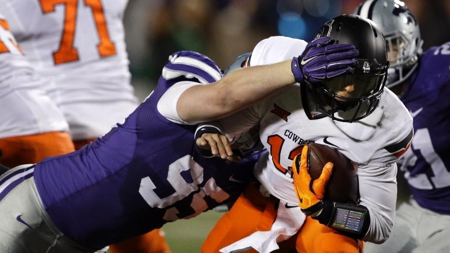 Oklahoma State quarterback Daxx Garman (12) is sacked by Kansas State defensive lineman Travis Britz (95) during the first half of an NCAA college football game in Manhattan, Kan., Saturday, Nov. 1, 2014. (AP Photo/Orlin Wagner)