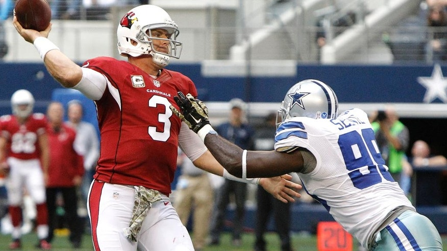 Arizona Cardinals quarterback Carson Palmer (3) passes as Dallas Cowboys defensive end George Selvie (99) defends during the second half of an NFL football game Sunday, Nov. 2, 2014, in Arlington, Texas. (AP Photo/Brandon Wade)