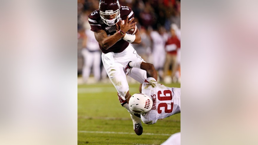 Mississippi State quarterback Dak Prescott (15) is tackled by Arkansas safety Rohan Gaines (26) after a short run in the first half of an NCAA college football game in Starkville, Miss., Saturday, Nov. 1, 2014. (AP Photo/Rogelio V. Solis)