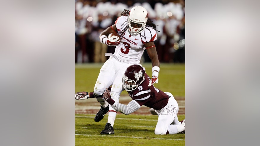 Arkansas running back Alex Collins (3) is tackled after a short gain by Mississippi State defensive back Justin Cox (9) but the play is nullified on a Arkansas holding penalty in the first half of an NCAA college football game in Starkville, Miss., Saturday, Nov. 1, 2014. (AP Photo/Rogelio V. Solis)