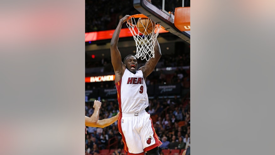 Miami Heat's Luol Deng (9) scores two points against the Toronto Raptors during the first half of an NBA basketball game in Miami, Sunday, Nov. 2, 2014. (AP Photo/Joel Auerbach)