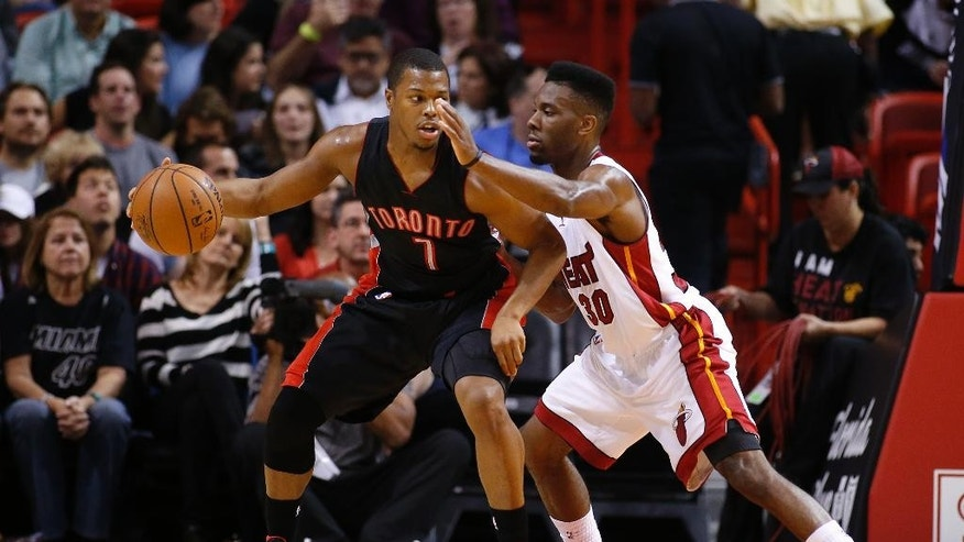 Toronto Raptors' Kyle Lowry (7) works against Miami Heat's Norris Cole (30) during the first half of an NBA basketball game in Miami, Sunday, Nov 2, 2014. (AP Photo/Joel Auerbach)