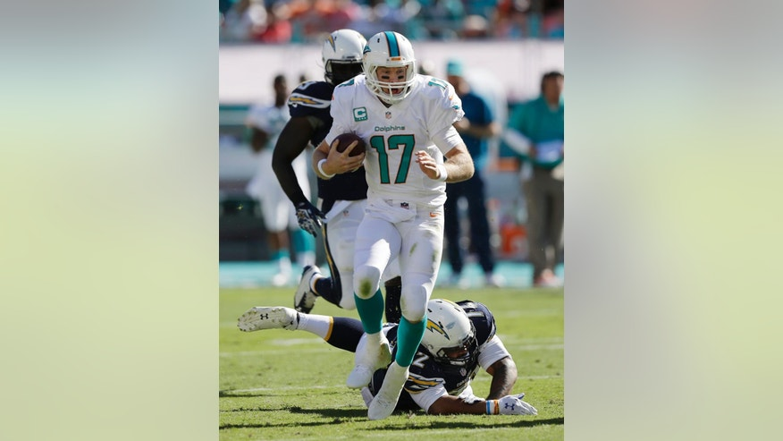 Miami Dolphins quarterback Ryan Tannehill (17) avoids a tackle by San Diego Chargers defensive end Tenny Palepoi (72) during the first half of an NFL football game, Sunday, Nov. 2, 2014, in Miami Gardens, Fla.  (AP Photo/Alan Diaz)