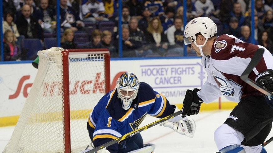 St. Louis Blues' goalie Brian Elliott (1) defends against Colorado Avalanche's John Mitchell (7) during the first period of an NHL hockey game, Saturday, Nov. 1, 2014, in St. Louis. (AP Photo/Bill Boyce)