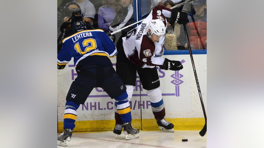 St. Louis Blues' Jori Lehtera (12), of Finland, and Colorado Avalanche's Erik Johnson (6) battle for the puck during the second period of an NHL hockey game, Saturday, Nov. 1, 2014, in St. Louis. (AP Photo/Bill Boyce)