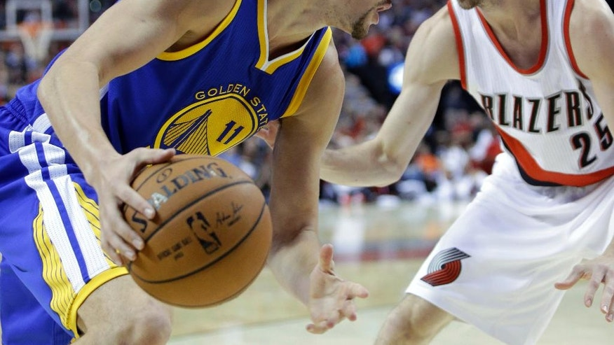 Golden State Warriors guard Klay Thompson, left, drives the baseline against Portland Trail Blazers guard Steve Blake during the first half of an NBA basketball game in Portland, Ore., Sunday, Nov. 2, 2014. (AP Photo/Don Ryan)