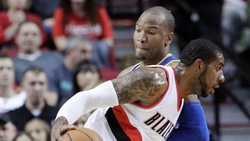Portland Trail Blazers forward LaMarcus Aldridge, front, drives on Golden State Warriors forward Marreese Speights during the first half of an NBA basketball game in Portland, Ore., Sunday, Nov. 2, 2014. (AP Photo/Don Ryan)