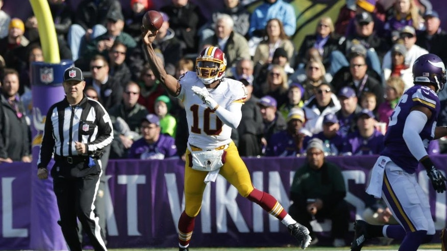 Washington Redskins quarterback Robert Griffin III throws a pass during the first half of an NFL football game against the Minnesota Vikings, Sunday, Nov. 2, 2014, in Minneapolis. (AP Photo/Jim Mone)