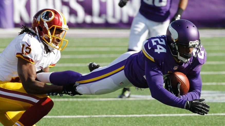 Minnesota Vikings cornerback Captain Munnerlyn (24) intercepts a pass in front of Washington Redskins wide receiver Andre Roberts, left, during the first half of an NFL football game, Sunday, Nov. 2, 2014, in Minneapolis. (AP Photo/Ann Heisenfelt)