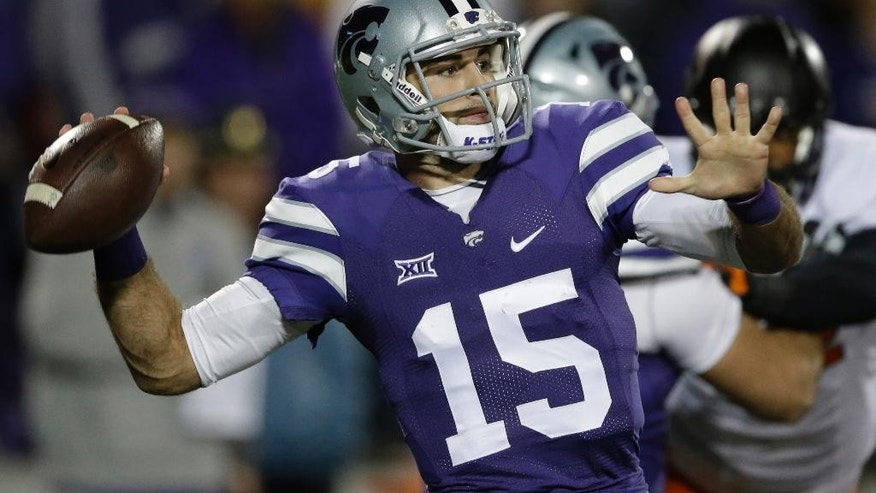 Kansas State quarterback Jake Waters (15) passes to a teammate during the first half of an NCAA college football game against Oklahoma State in Manhattan, Kan., Saturday, Nov. 1, 2014. (AP Photo/Orlin Wagner)