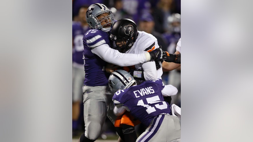 Oklahoma State quarterback Daxx Garman (12) is tackled by Kansas State defensive end Jordan Willis (75) and defensive back Randall Evans (15) during the first half of an NCAA college football game in Manhattan, Kan., Saturday, Nov. 1, 2014. (AP Photo/Orlin Wagner)