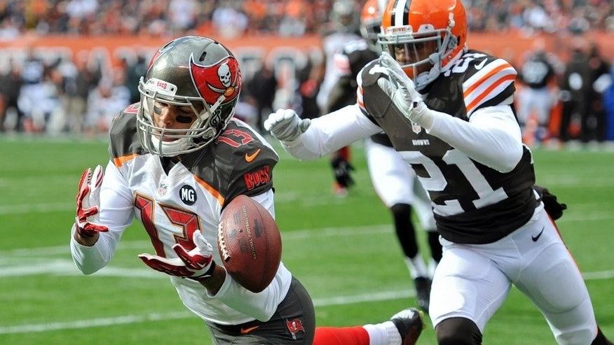 Tampa Bay Buccaneers wide receiver Mike Evans (13) can't catch a pass under pressure from Cleveland Browns cornerback Justin Gilbert (21) in the first quarter of an NFL football game, Sunday, Nov. 2, 2014, in Cleveland. (AP Photo/David Richard)