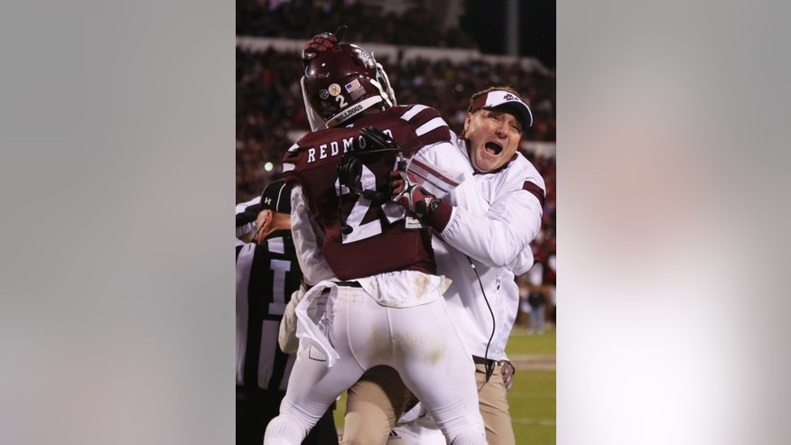 Mississippi State football coach Dan Mullen celebrates with Mississippi State defensive back Will Redmond (2) after he intercepted a pass in the end zone in the final seconds of the second half of an NCAA college football game in Starkville, Miss., Saturday, Nov. 1, 2014. No. 1 Mississippi State won 17-10. (AP Photo/Rogelio V. Solis)