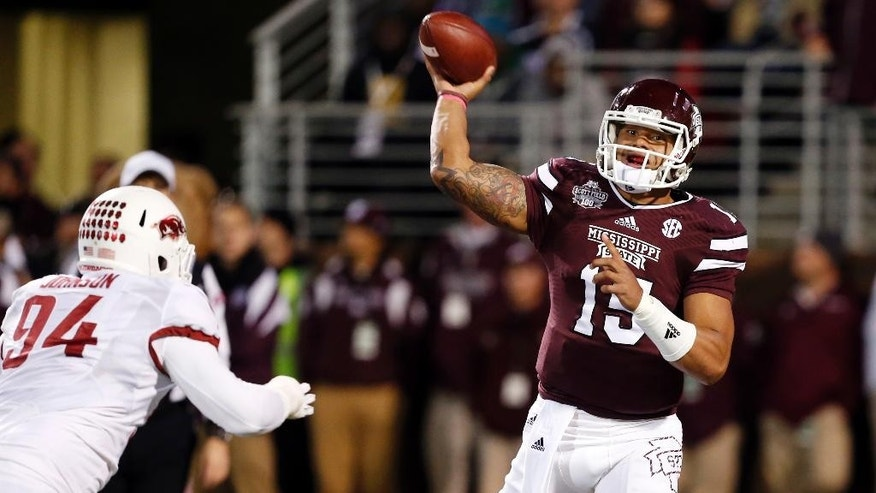Mississippi State quarterback Dak Prescott (15) looks for an open receiver as he is pressured while trying to pass by Arkansas defensive tackle Taiwan Johnson (94) in the first half of an NCAA college football game in Starkville, Miss., Saturday, Nov. 1, 2014. (AP Photo/Rogelio V. Solis)