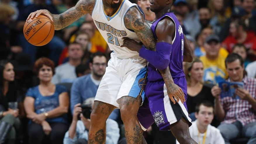 Denver Nuggets forward Wilson Chandler, left, works the ball inside for shot as Sacramento Kings guard Darren Collison covers in the first half of an NBA basketball game in Denver on Monday, Nov. 3, 2014. (AP Photo/David Zalubowski)