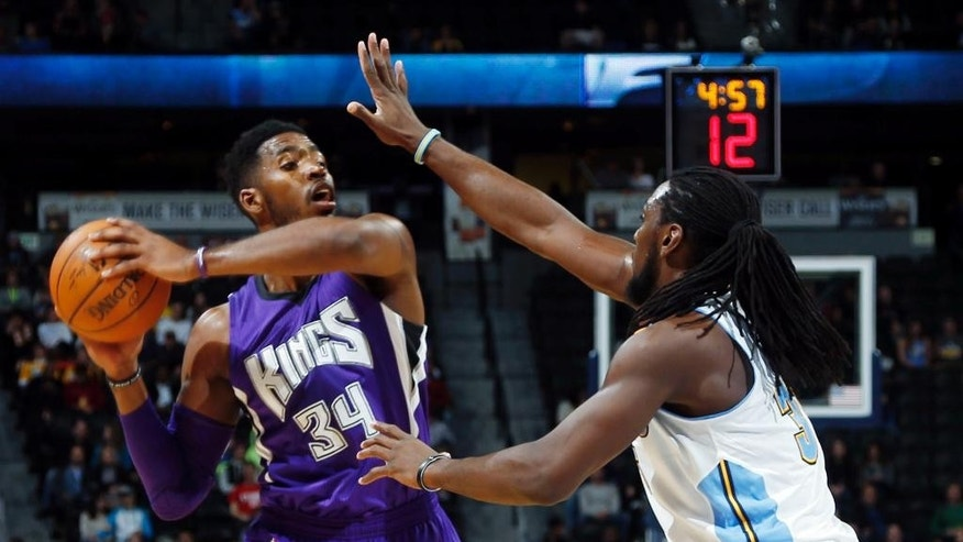 Sacramento Kings forward Jason Thompson, left, looks to pass ball as Denver Nuggets forward Kenneth Faried covers in the first half of an NBA basketball game in Denver on Monday, Nov. 3, 2014. (AP Photo/David Zalubowski)