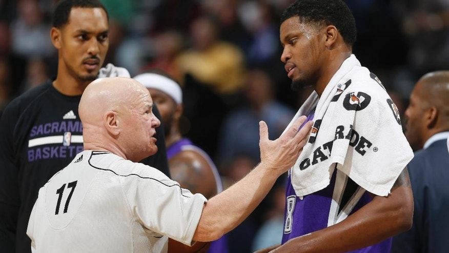 Sacramento Kings forward Rudy Gay, right, confers with referee Joey Crawford, left, as center Ryan Hollins looks on as the Kings face the Denver Nuggets in the first quarter of an NBA basketball game in Denver on Monday, Nov. 3, 2014. (AP Photo/David Zalubowski)