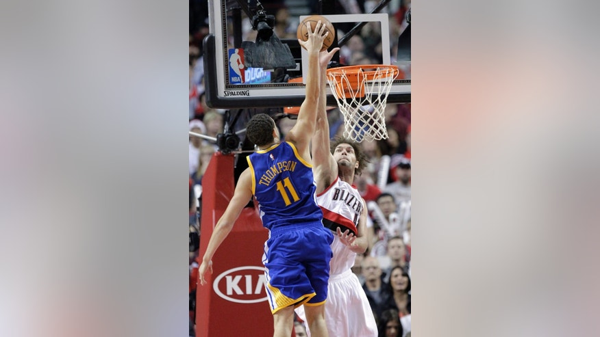 Golden State Warriors guard Klay Thompson, left, goes for a dunk shot to score against Portland Trail Blazers center Robin Lopez during the second half of an NBA basketball game in Portland, Ore., Sunday, Nov. 2, 2014. Thompson led the Warriors in scoring with 29 points as they beat the Trail Blazers 95-90. (AP Photo/Don Ryan)