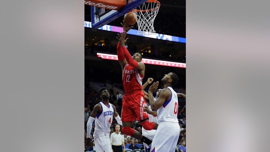 Houston Rockets' Dwight Howard (12) goes up for a shot against Philadelphia 76ers' Nerlens Noel (4) and Brandon Davies (0) during the first half of an NBA basketball game, Monday, Nov. 3, 2014, in Philadelphia. (AP Photo/Matt Slocum)