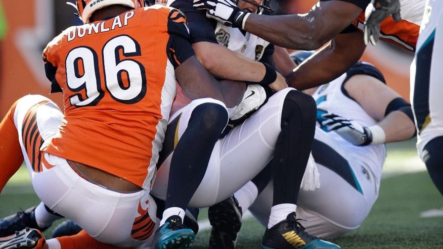 Jacksonville Jaguars quarterback Blake Bortles, center, is sacked by Cincinnati Bengals defensive end Carlos Dunlap, left, and defensive tackle Geno Atkins during the first half of an NFL football game in Cincinnati, Sunday, Nov. 2, 2014. (AP Photo/AJ Mast)
