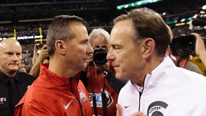 FILE - In this Dec. 7, 2013, file photo, Michigan State head coach Mark Dantonio, right, is congratulated by Ohio State head coach Urban Meyer following the Big Ten Conference championship NCAA college football game in Indianapolis. After beating up on lesser opponents for six straight games, No. 13 Ohio State gets to see just how good it is. Up next, No. 7 Michigan State. (AP Photo/AJ Mast, File)