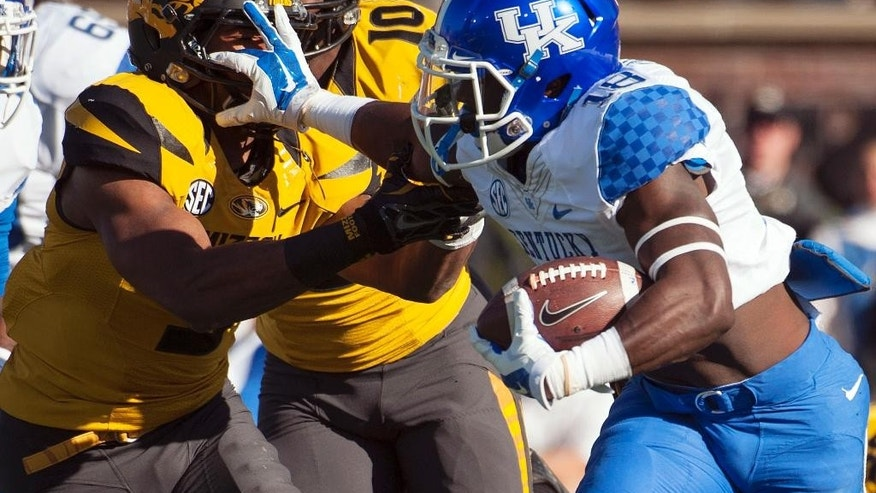 Kentucky running back Stanley Williams, right, stiff arms Missouri's Braylon Webb as he runs during the first quarter of an NCAA college football game Saturday, Nov. 1, 2014, in Columbia, Mo. (AP Photo/L.G. Patterson)