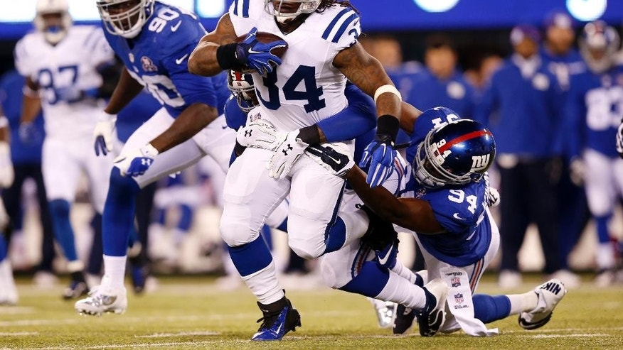 New York Giants defensive end Mathias Kiwanuka (94) tackles Indianapolis Colts running back Trent Richardson (34) during the first half of an NFL football game Monday, Nov. 3, 2014, in East Rutherford, N.J. (AP Photo/Kathy Willens)