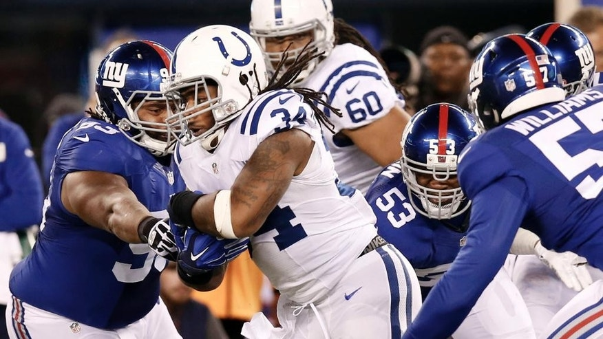 Indianapolis Colts running back Trent Richardson (34) rushes past New York Giants defensive tackle Mike Patterson (93) during the first half of an NFL football game Monday, Nov. 3, 2014, in East Rutherford, N.J. (AP Photo/Kathy Willens)