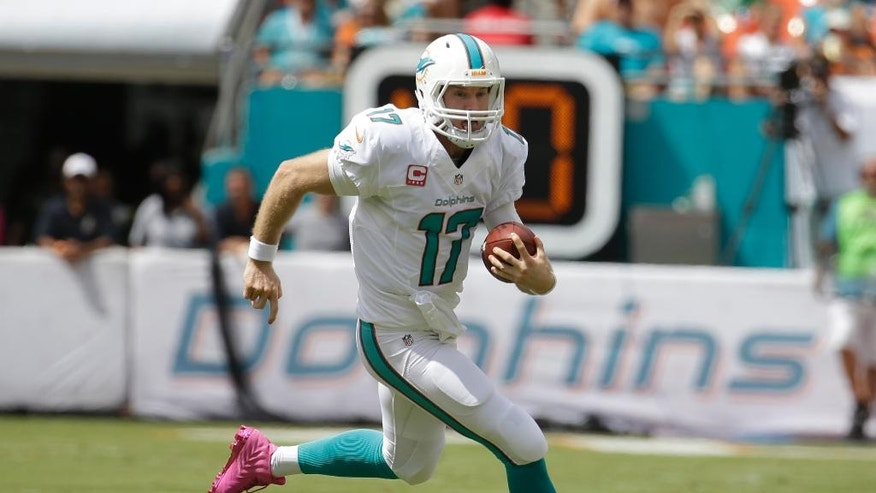 FILE - In this Oct. 12, 2014, file photo, Miami Dolphins quarterback Ryan Tannehill (17) runs with the ball during the first half of an NFL football against the Green Bay Packers in Miami Gardens, Fla. While Tannehill haven't missed a start since the beginning of his rookie season in 2012, risking the quarterback's health remains part of the read-option debate. (AP Photo/Lynne Sladky, File)