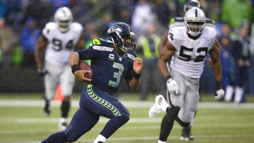 FILE - In this Nov. 2, 2014, file photo, Seattle Seahawks quarterback Russell Wilson scrambles in the second half of an NFL football game against the Oakland Raiders in Seattle. Wilson is averaging 49 yards per game and 7.6 per carry, both career highs. (AP Photo/Stephen Brashear, File)