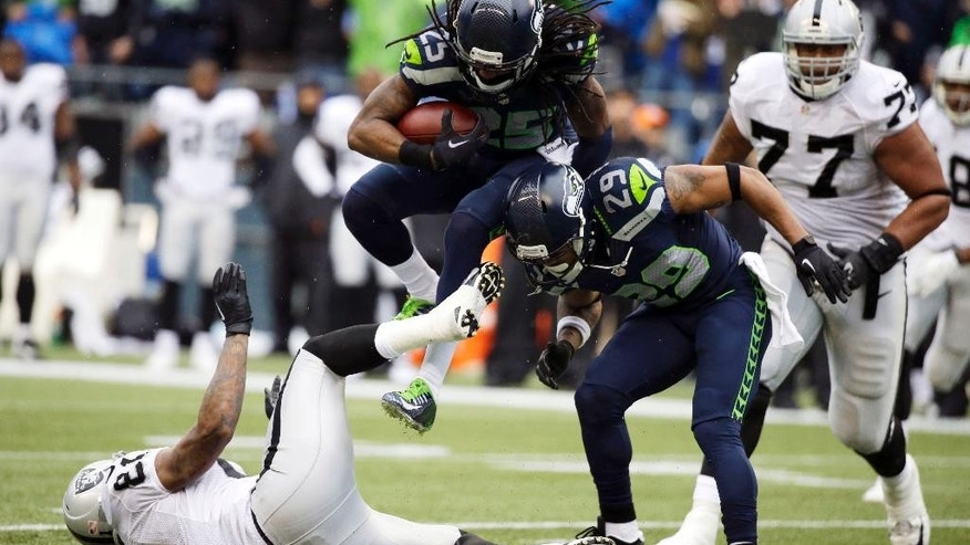 Seattle Seahawks cornerback Richard Sherman jumps over Oakland Raiders' tight end Mychal Rivera, left, and Seahawks' Earl Thomas (29) after Sherman made an interception in the first half of an NFL football game Sunday, Nov. 2, 2014, in Seattle. (AP Photo/Elaine Thompson)