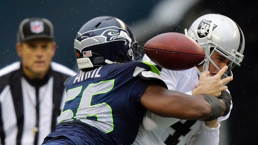 Seattle Seahawks defensive end Cliff Avril, left, causes Oakland Raiders quarterback Derek Carr to fumble in the first half of an NFL football game, Sunday, Nov. 2, 2014, in Seattle. The Raiders recovered the ball. (AP Photo/Stephen Brashear)