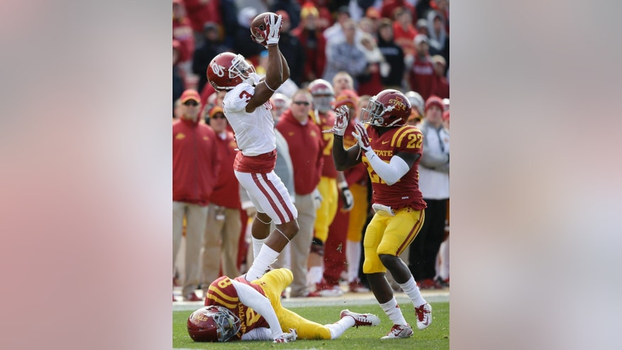 Oklahoma wide receiver Sterling Shepard (3) catches a pass over Iowa State defensive back Kenneth Lynn (8) and defensive back T.J. Mutcherson (22) during the first half of an NCAA college football game, Saturday, Nov. 1, 2014, in Ames, Iowa. (AP Photo/Charlie Neibergall)