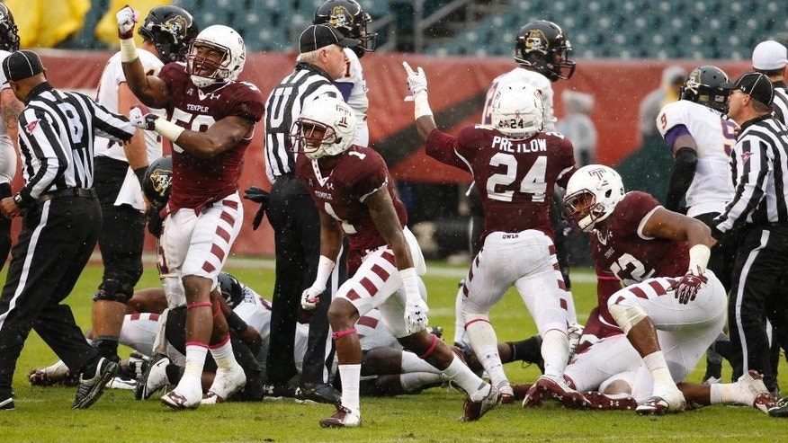 Temple defensive lineman Haason Reddick, left, defensive back Tavon Young, center, and defensive back Jihaad Pretlow, right, celebrates a fumble recovery during the first half an NCAA college football game against the East Carolina, Saturday, Nov. 1, 2014, in Philadelphia. (AP Photo/Chris Szagola)