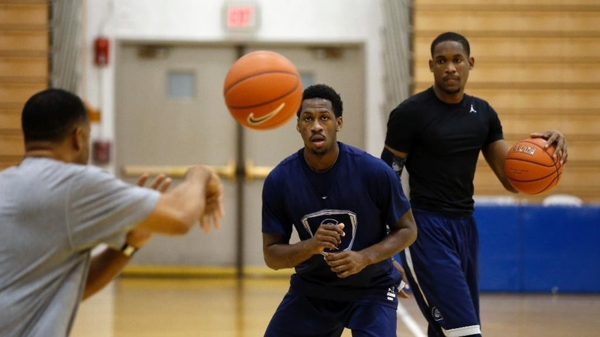 L.J. Peak, center, prepares to catch a pass during practice during Georgetown University basketball media day, Thursday, Oct. 23, 2014, in Washington. (AP Photo/Alex Brandon)