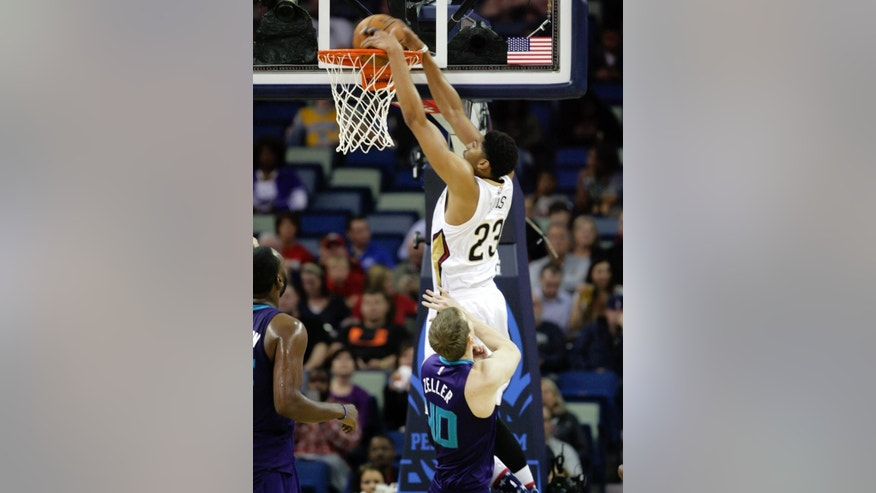 New Orleans Pelicans forward Anthony Davis (23) dunks against Charlotte Hornets' Cody Zeller (40) during the first half of an NBA basketball game in New Orleans, Tuesday, Nov. 4, 2014. (AP Photo/Scott Threlkeld)