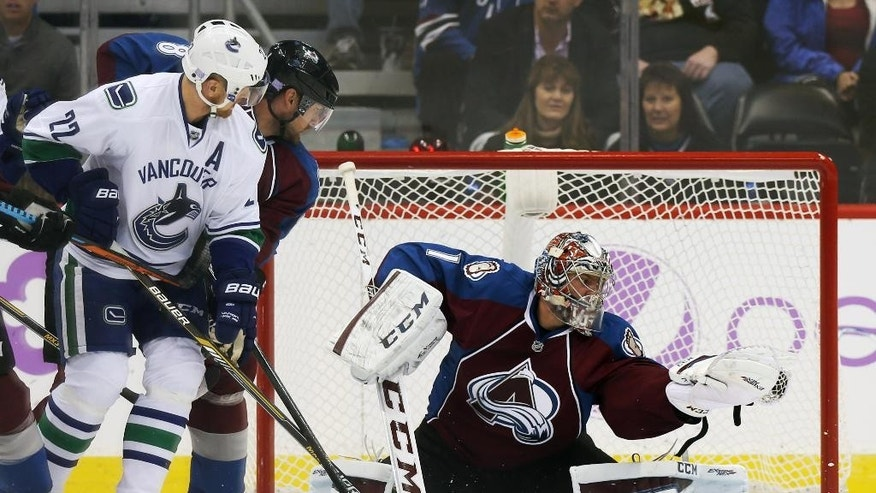 Colorado Avalanche goalie Semyon Varlamov, right, of Russia, makes a glove save of a redirected shot off the stick of Vancouver Canucks left wing Daniel Sedin, front left, of Sweden, as Avalanche defenseman Jan Hejda, back left, of the Czech Republic, covers in the first period of an NHL hockey game in Denver on Tuesday, Nov. 4, 2014. (AP Photo/David Zalubowski)