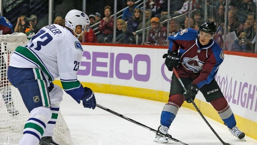 Vancouver Canucks defenseman Alexander Edler, left, of Sweden, pursues Colorado Avalanche center Matt Duchene as he tries to pass the puck in the first period of an NHL hockey game in Denver on Tuesday, Nov. 4, 2014. (AP Photo/David Zalubowski)