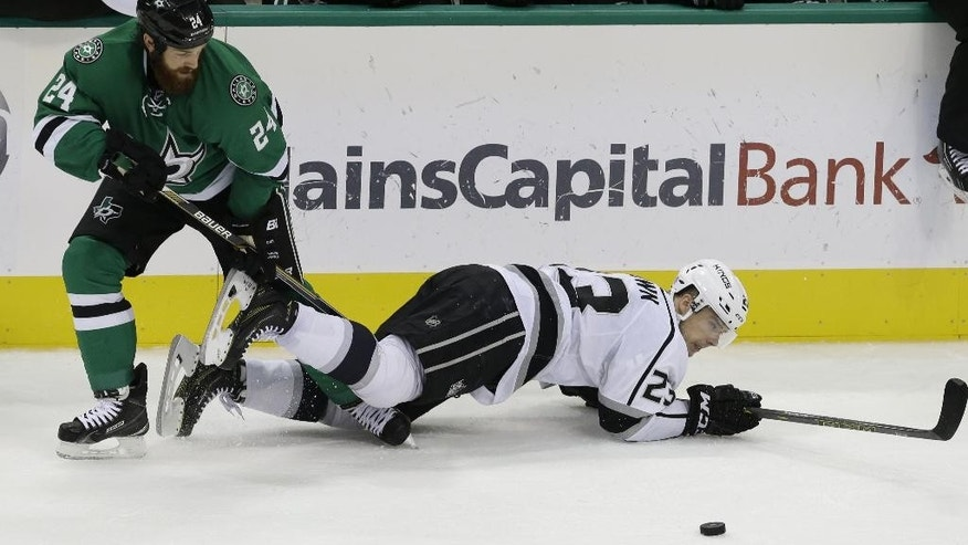 Los Angeles Kings right wing Dustin Brown (23) is knocked to the ice by Dallas Stars defenseman Jordie Benn (24) during the second period of an NHL hockey game Tuesday, Nov. 4, 2014, in Dallas. (AP Photo/LM Otero)