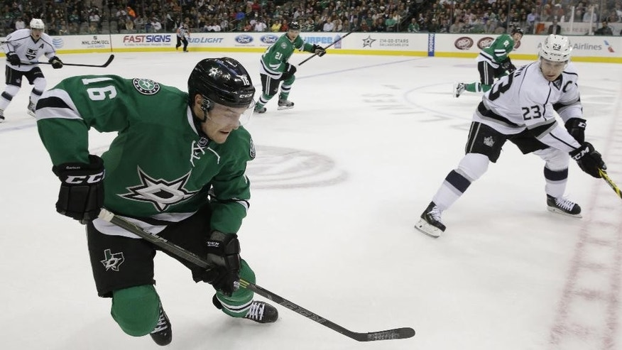 Dallas Stars left wing Ryan Garbutt (16) takes control of the puck against Los Angeles Kings right wing Dustin Brown (23) during the first period of an NHL hockey game Tuesday, Nov. 4, 2014, in Dallas. (AP Photo/LM Otero)