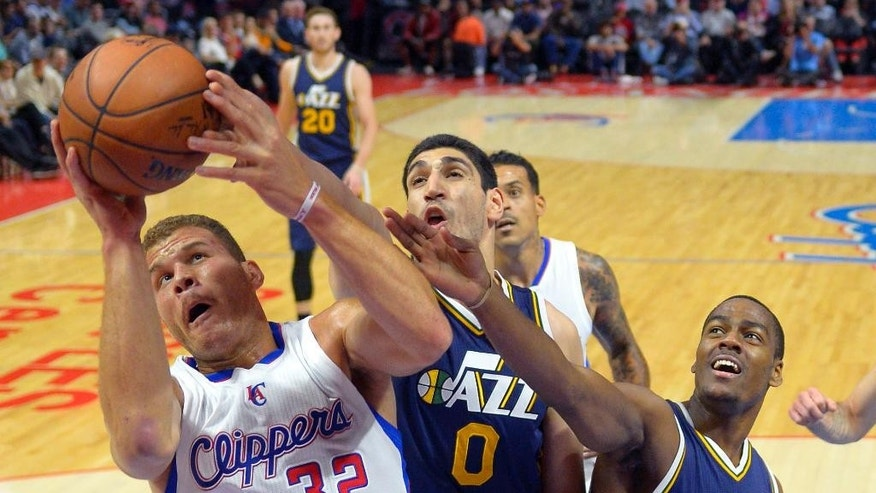 Los Angeles Clippers forward Blake Griffin, left, grabs a rebound away from Utah Jazz center Enes Kanter, center, and guard Alec Burks during the first half of an NBA basketball game, Monday, Nov. 3, 2014, in Los Angeles. (AP Photo/Mark J. Terrill)
