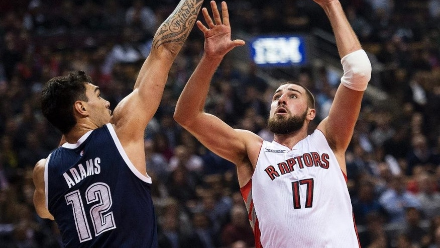 Toronto Raptors forward Jonas Valanciunas (17) drives the net against Oklahoma City Thunder forward Steven Adams (12) during first half NBA basketball action in Toronto on Tuesday, Nov. 4, 2014. (AP Photo/The Canadian Press, Nathan Denette)