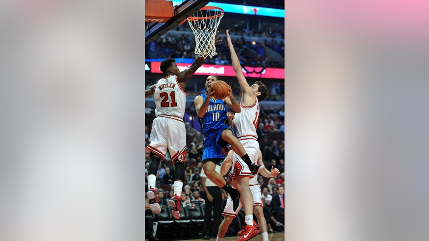 Orlando Magic's Evan Fournier (10), of France,  goes up for a shot against Chicago Bulls' Pau Gasol (16), of Spain, and Jimmy Butler (21) during the first half of an NBA basketball game in Chicago, Tuesday, Nov. 4, 2014. (AP Photo/Paul Beaty)
