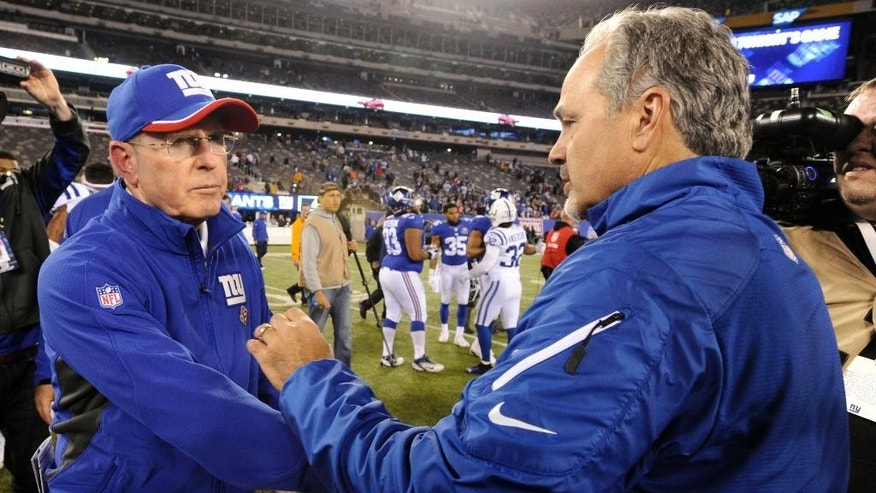 New York Giants head coach Tom Coughlin, left, greets with Indianapolis Colts head coach Chuck Pagano after an NFL football game Monday, Nov. 3, 2014, in East Rutherford, N.J. The Colts won 40-24. (AP Photo/Bill Kostroun)