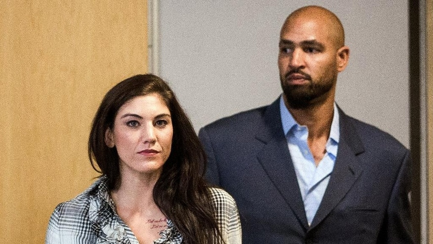 U.S. women's soccer star Hope Solo, left, and her husband, former  Seattle Seahawks football player Jerramy Stevens leave Kirkland Municipal Court Tuesday, Nov. 4, 2014, in Kirkland, Wash. The Seattle Times reports Kirkland Municipal Court Judge Michael Lambo set a Jan. 6 trial date on misdemeanor domestic violence charges for Solo during a brief hearing Tuesday. (AP Photo/seattlepi.com,  Jordan Stead) MAGS OUT; NO SALES; SEATTLE TIMES OUT; TV OUT; MANDATORY CREDIT