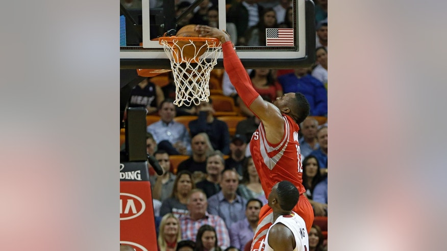 Houston Rockets center Dwight Howard (12) dunks against the Miami Heat in the first half of an NBA basketball game, in Miami,Tuesday, Nov. 4, 2014. (AP Photo/Alan Diaz)