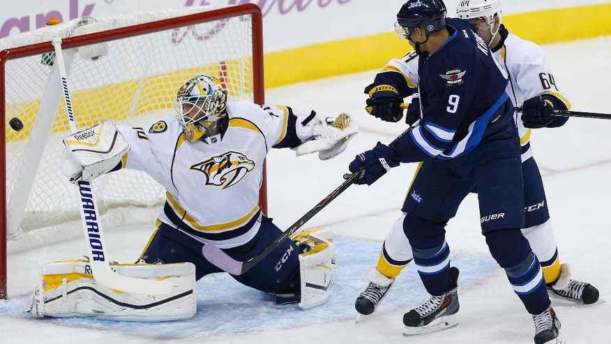 Winnipeg Jets' Evander Kane (9) watches as a shot by Mark Scheifele goes past Nashville Predators goaltender Carter Hutton (30) while Victor Bartley (64) defends during during the first period of an NHL hockey game Tuesday, Nov. 4, 2014, in Winnipeg, Manitoba. (AP Photo/The Canadian Press, John Woods)