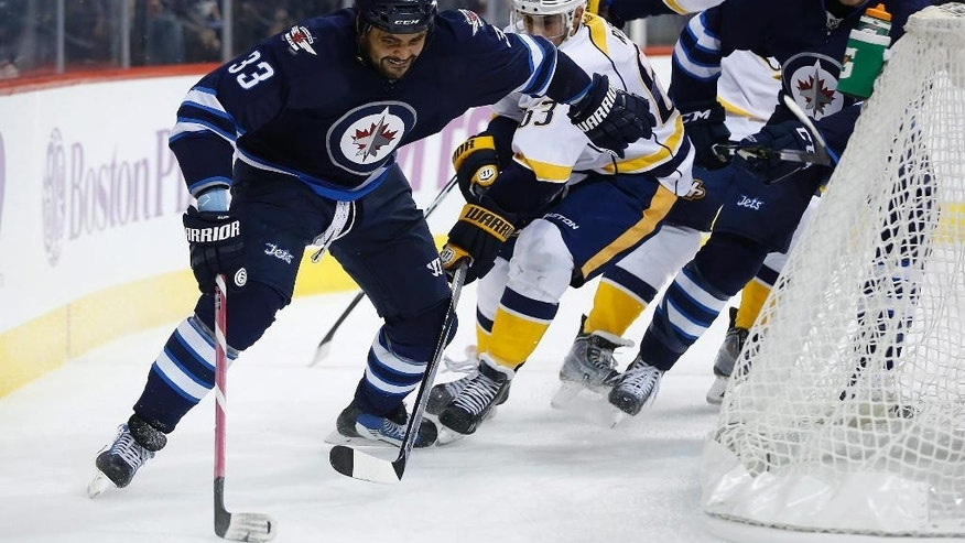 Winnipeg Jets' Dustin Byfuglien (33) one-hands the puck around the net with Nashville Predators' Mike Ribeiro (63) in pursuit during the second period of an NHL hockey game Tuesday, Nov. 4, 2014, in Winnipeg, Manitoba. (AP Photo/The Canadian Press, John Woods)