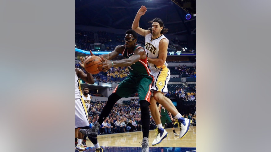Milwaukee Bucks center Larry Sanders, left, grabs a rebound in front of Indiana Pacers forward Luis Scola during the first half of an NBA basketball game in Indianapolis, Tuesday, Nov. 4, 2014.(AP Photo/R Brent Smith)